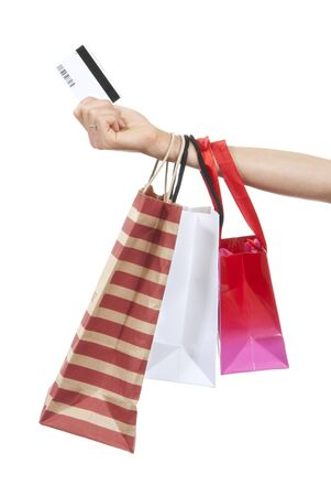 Hand with credit gift card and shopping bags isolated on a white background
