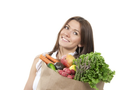 Happy young woman with supermarket shopping bag full of groceries, cucumbers, salad, asparagus, radish, avocado, lemon, mango, carrots on white background photo