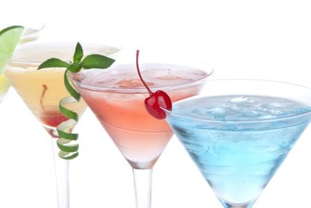 Zomer Tropical Martini-cocktails met wodka, appel en perzik likeur, ananas en cranberry sap, limoen, citroen, Blue Curaçao, maraschino kersen, en orchidee die op een witte achtergrond