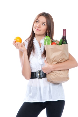 Happy young woman holding a paper shopping bag full of groceries, mango, salad, asparagus,tomatoes, papper, orange, bottle of wine on white background Stock Photo - 12118103