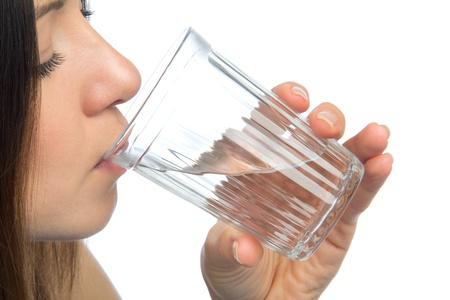 Vrouw drinkwater geà ¯ soleerd tegen een witte achtergrond Stockfoto