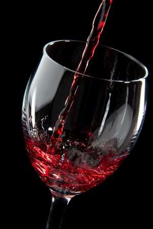 Red wine splash being poured into a wine glass on black background photo