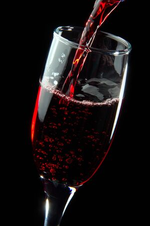 Red wine splash being poured into a wine glass on black background Stock Photo - 12118146