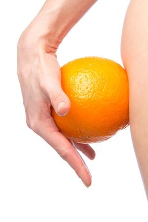 Hip en oranje in de hand cellulitis liposuctie gewichtsverlies besturingsconcept geïsoleerd tegen witte achtergrond Stockfoto