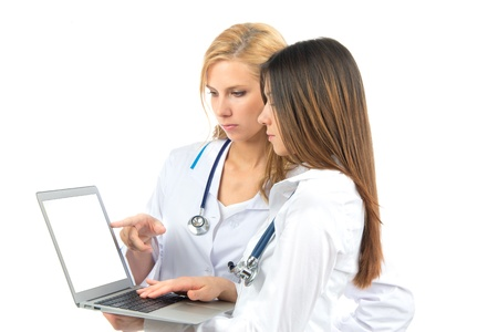 Two woman doctor and nurse research and hold laptop computer in hands finger pointing digital screen isolated on a white background