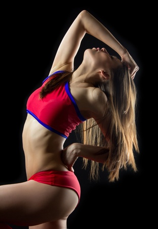 Beautiful woman cheerleader dancer from cheerleading team with long hair and slim body against black background photo