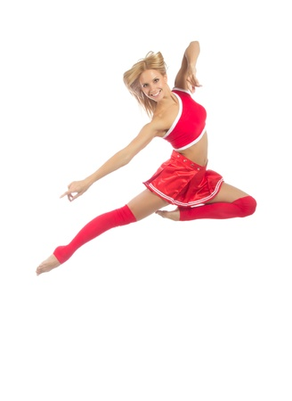 Happy female cheerleader dancer from cheerleading team jumping in mid air against white background  Фото со стока