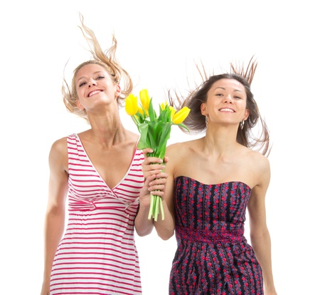 Two pretty happy girls with bouquet of tulips flowers walking smiling isolated on a white background photo