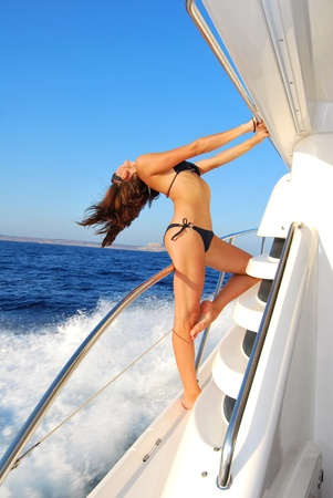 Pretty young slim sexy brunette woman in sunglasses sailboat yacht in black stylish bikini on private speed-boat on vacation in summer time happy sailing in Mediterranean sea  photo