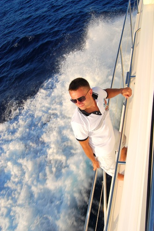 Young Sailor relaxing happily on the vacation sailboat yacht standing on a deck  having a rest on summer boat over blue ocean wave splashes background  Banco de Imagens