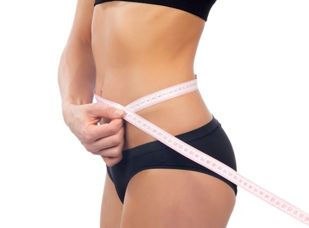 Athletic fit slim female measuring her waist metric tape measure after a diet isolated over white background  photo