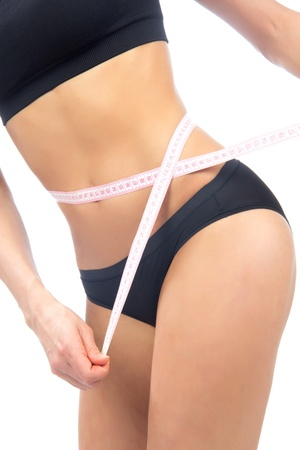 body conscious: Athletic fit slim woman measuring her waist metric tape measure after a diet isolated over white background