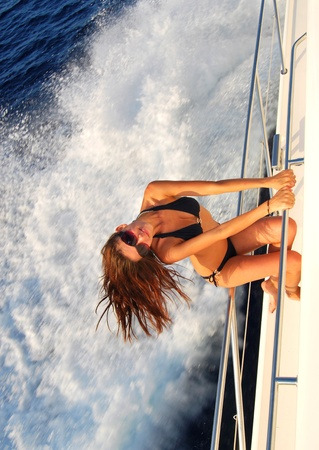Pretty young slim sexy brunette woman in sunglasses sailboat yacht in black stylish bikini on private speed-boat on vacation in summer time happy sailing in Mediterranean sea