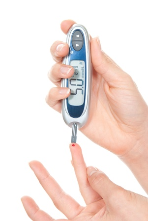 Diabetes patient hands measuring glucose level blood test using ultra mini glucometer and small drop of blood from finger and test strips isolated on a white background Stock Photo