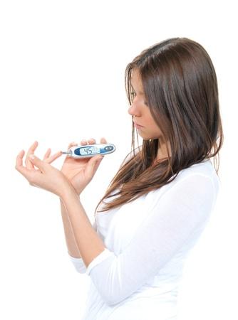 Diabetes patiënt vrouw het meten van glucose niveau bloedonderzoek met behulp van ultra mini glucometer en kleine druppel bloed uit de vinger en teststrips geïsoleerd op een witte achtergrond Stockfoto