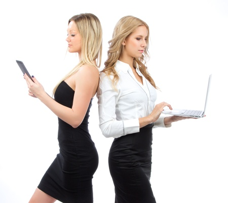 Two business woman with new wireless digital ebook device and laptop smiling isolated over white background photo
