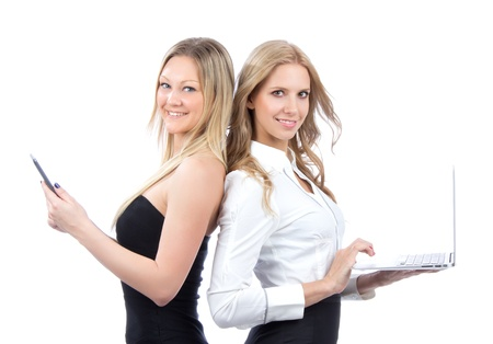 personal assistant: Two business woman with new wireless digital ebook device and laptop smiling isolated over white background