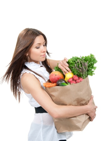 grocer: Happy young woman holding a grocery shopping bag full of groceries, mango, salad, asparagus, radish, avocado, lemon, carrots on white background