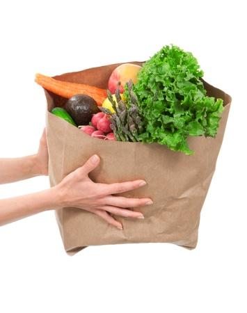 Handen die een boodschappentas vol boodschappen, mango, sla, asperges, radijs, avocado, citroen, wortelen op een witte achtergrond