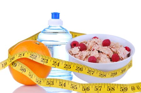 Diet weight loss food breakfast concept with tape measure natural orange, corn healthy flakes with fresh raspberries on a white background  photo