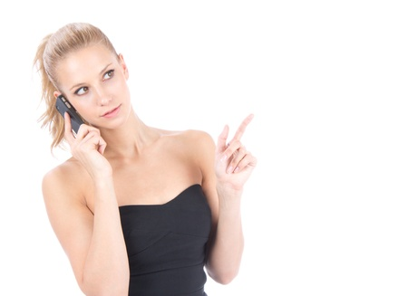 Business woman calling by mobile phone and pointing hand finger at corner with copyspace isolated on a white background photo