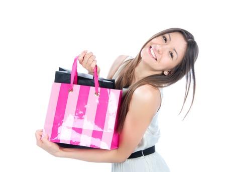 Mooie jonge vrouw met boodschappentassen cadeautjes kopen, lacht en kijkt naar de camera geà ¯ soleerd op een witte achtergrond