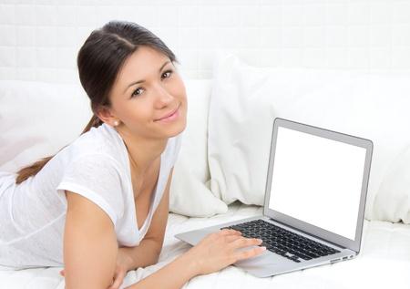 Jonge mooie vrolijke vrouw liggend op de bank met moderne laptop computer en glimlachen