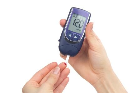 Afhankelijk eerste type diabetes patiënt het meten van glucose niveau bloedonderzoek met behulp van ultra mini glucometer en kleine druppel bloed uit de vinger en teststrips geïsoleerd op een witte achtergrond Stockfoto