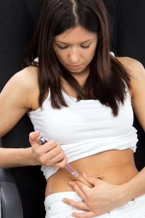 Diabetes woman patient make an abdomen subcutaneous syringe insulin injection with needle on a sofa at home photo