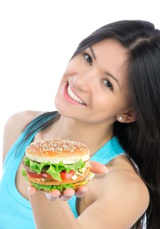 nice food: Молодая женщина с вкусной нездоровой фаст-фуд гамбургер в руке получения готовой к употреблению, изолированных на белом фоне. Сосредоточиться на руку гамбургер WITN.