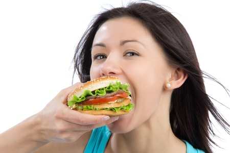 fast eat: Young woman eating tasty fast food unhealthy burger in hand getting ready to eat isolated on a white background.