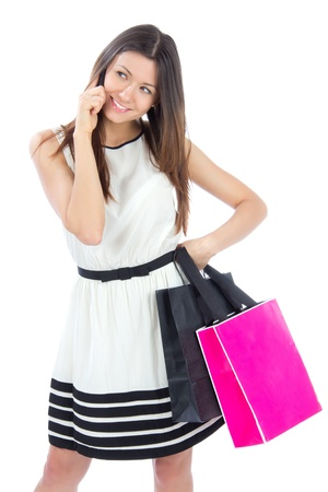 Pretty young woman with shopping bags buying presents, smiling and looking at the camera isolated on a white background photo