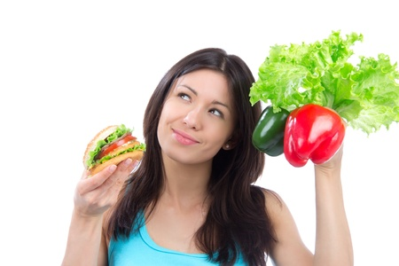 unhealthy: Young woman comparing tasty fast food unhealthy burger or hamburger and healthy fresh peppers and salad isolated on a white backgroung Stock Photo