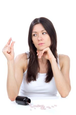 pills in hand: La mujer con la mirada de dolor de cabeza en tabletas de pastillas de medicina en la mesa contra el fondo blanco