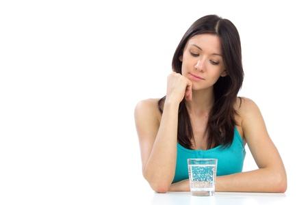 여자는 테이블에 유리 물을 마시는 준비. 흰색 배경에 건강 한 무게 손실 개념