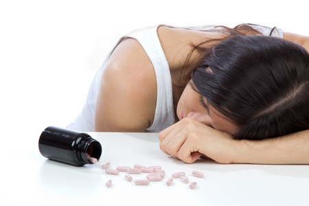 Woman with headache or stress depression on drug pills medicine tablets lying on table against white background Stock Photo - 13585700