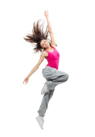 Modern teenage girl dancer dancing hip-hop and jumping with windy hair smiling isolated on a white background
