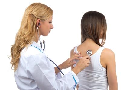 Doctor vrouw auscultating jonge patiënt door stethoscoop geïsoleerd op een witte achtergrond Stockfoto