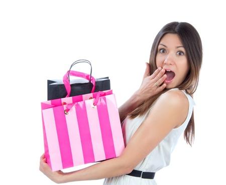 chicas de compras: Bastante joven mujer con bolsas de la compra con �xito despu�s de las compras, sonriendo y mirando a la c�mara sobre un fondo blanco Foto de archivo