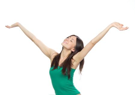 Jonge mooie vrouw in een groene top met armen open gevoel vrijheid en geluk geïsoleerd op een witte achtergrond Stockfoto