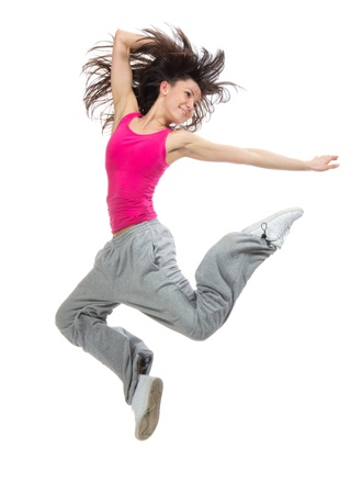 dancing pose: pretty modern slim hip-hop style teenage girl jumping dancing isolated on a white studio background