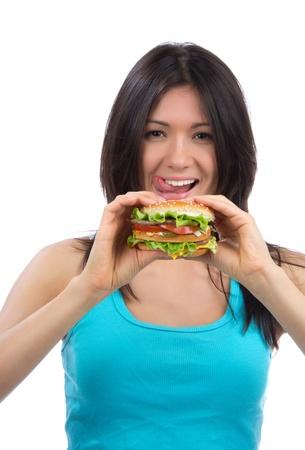 nice food: Молодая женщина с вкусной нездоровой фаст-фуда Burger в руки голодного получения готовой к употреблению, изолированных на белом фоне Фото со стока