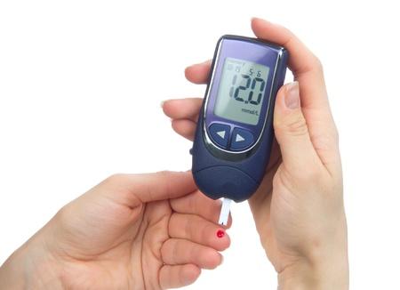 Diabetes patiënt prikte vinger naar een glucose niveau in het bloed test door nieuwe slimme glucometer geïsoleerd op een witte achtergrond te meten Stockfoto