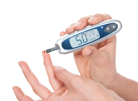 Diabetes meten glucose niveau bloedtest met behulp van ultra mini glucometer en kleine druppel bloed van vinger en test strips geïsoleerd op een witte achtergrond