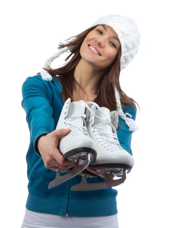 patinaje: Mujer joven que muestra patines de hielo para la actividad deportiva de patinaje de hielo de invierno en el sombrero blanco sonriente aislados sobre un fondo blanco