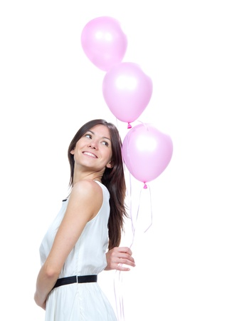 baloon: Young happy girl with pink balloons as a present for birthday party smiling and looking at the corner on a white background
