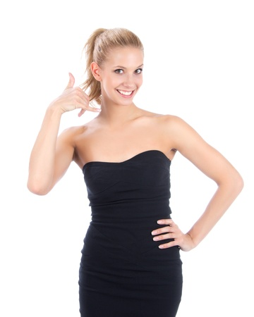 Pretty blonde woman showing the call me sign like talking on the mobile phone, smiling and looking on a white background photo