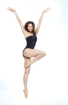 白のスタジオの背景上に分離されてかなりスリム ジャズ現代的なスタイルの女性バレエ ダンサー ポーズ