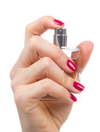 Woman hand spraying perfume. Focus on hand with red manicure and perfume bottle isolated on a white background photo