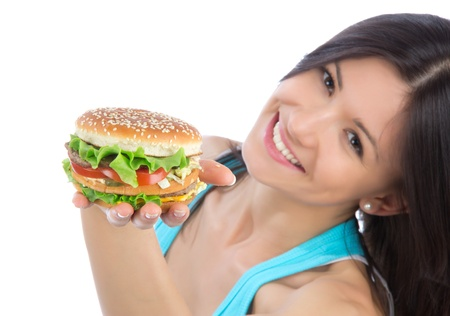large woman: Young woman with tasty fast food unhealthy burger sandwich in hand getting ready to eat isolated on a white background. Focus on hand witn hamburger. Stock Photo